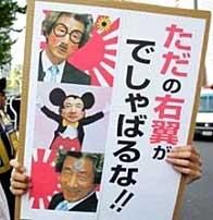 Protestor in Tokyo carries a sign of Koizumi that reads -Mind Your Own Business, Rightist!